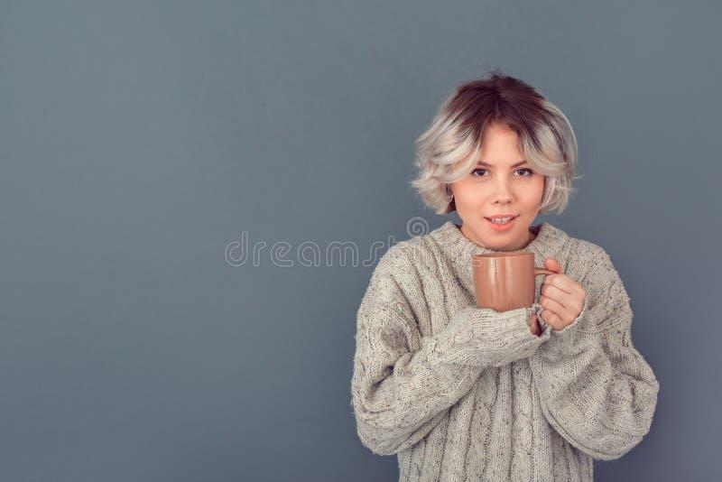 Jeune femme dans un chandail de laine d'isolement sur le lait chaud de mur de concept gris d'hiver image stock