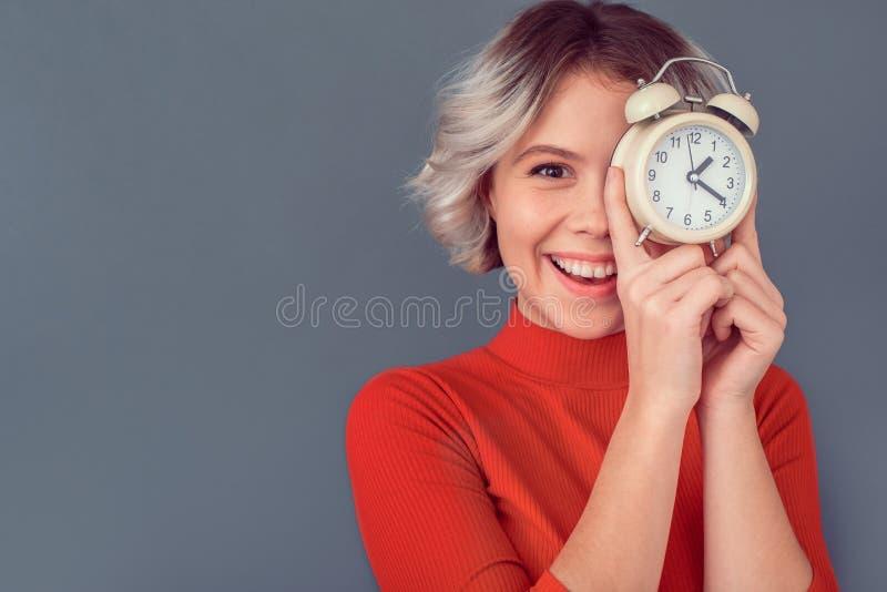 Jeune femme dans un chemisier rouge d'isolement sur la gestion du temps grise de mur image libre de droits