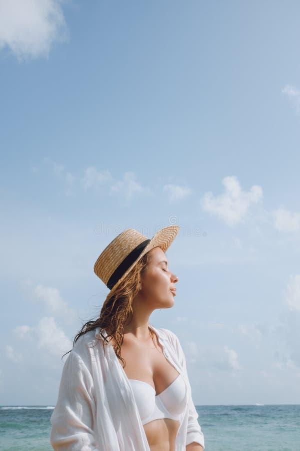 Jeune femme dans un maillot de bain et un chapeau blancs prenant un bain de soleil sur la plage photographie stock