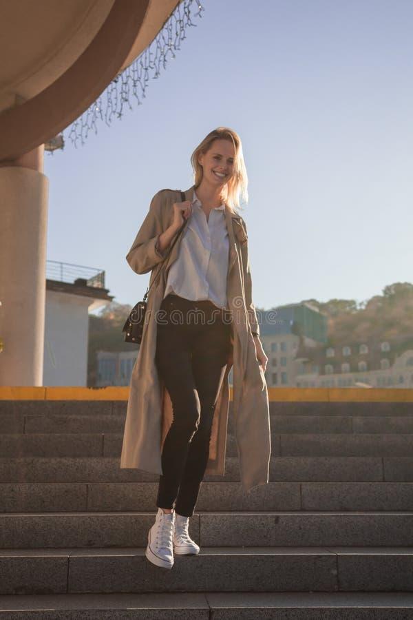 Jeune femme dans un manteau élégant de ressort en verres à la mode dans un T-shirt blanc dans un sac à main en cuir noir marchant photo libre de droits