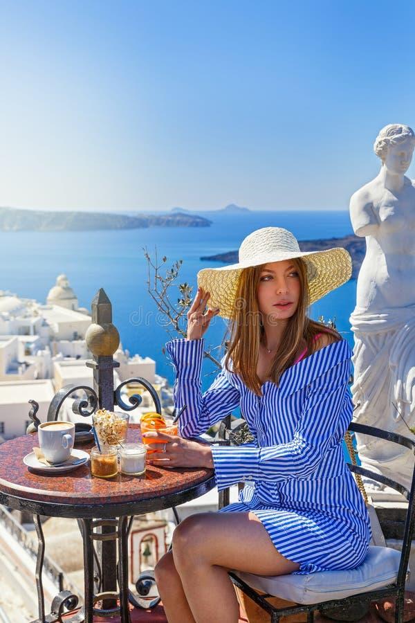 Jeune femme dans un restaurant au-dessus de la mer photographie stock libre de droits