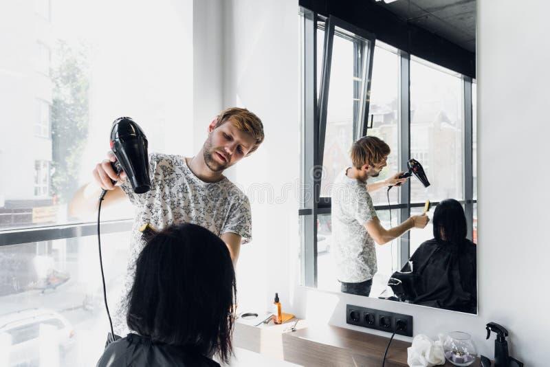 Jeune femme dans un salon de cheveu Cheveux de séchage masculins beaux de coiffeur avec le sèche-cheveux photographie stock libre de droits