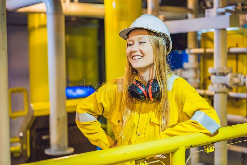 Jeune femme dans un uniforme jaune, les verres et le casque de travail dans le milieu industriel, la plateforme pétrolière ou l'u image stock