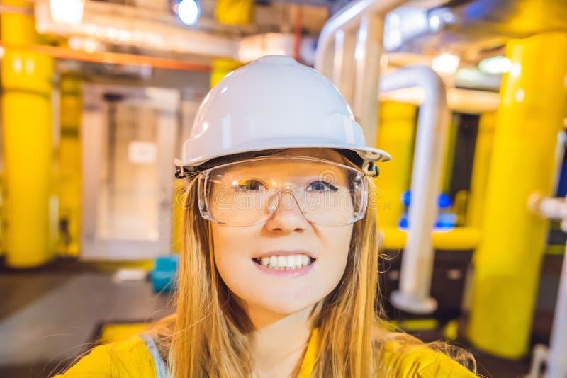 Jeune femme dans un uniforme jaune, les verres et le casque de travail dans le milieu industriel, la plateforme p?troli?re ou l'u photographie stock libre de droits