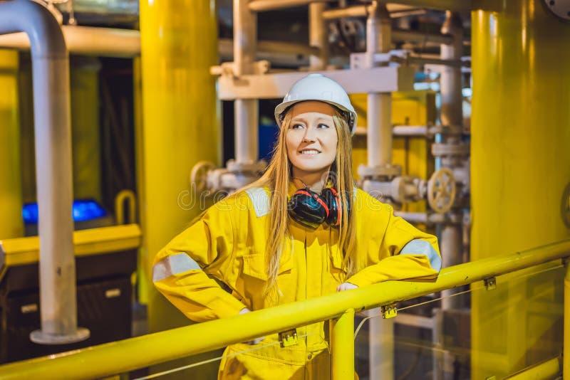 Jeune femme dans un uniforme jaune, les verres et le casque de travail dans le milieu industriel, la plateforme p?troli?re ou l'u photo libre de droits