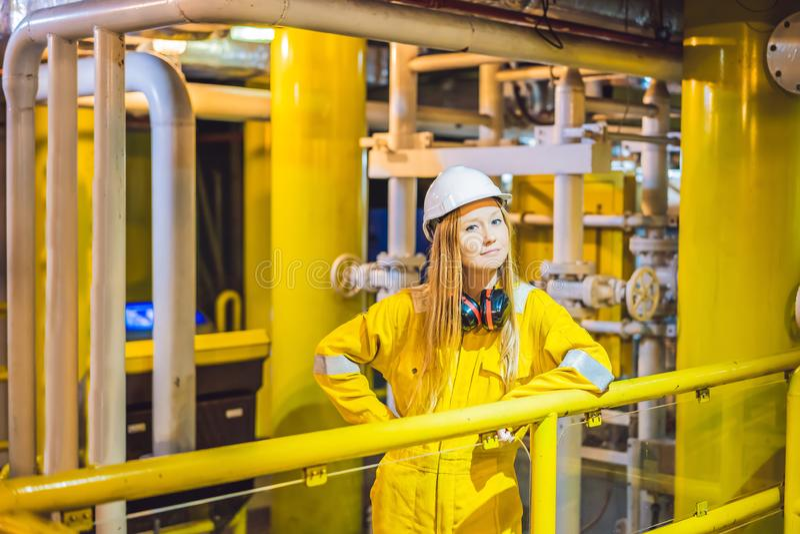 Jeune femme dans un uniforme jaune, les verres et le casque de travail dans le milieu industriel, la plateforme p?troli?re ou l'u photographie stock