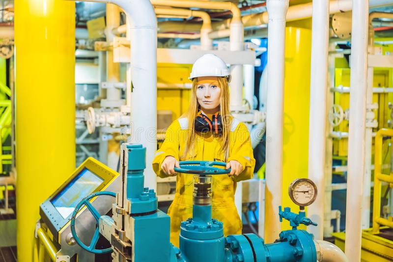 Jeune femme dans un uniforme jaune, les verres et le casque de travail dans le milieu industriel, la plateforme p?troli?re ou l'u images libres de droits