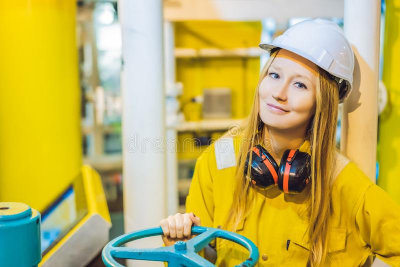 Jeune femme dans un uniforme jaune, les verres et le casque de travail dans le milieu industriel, la plateforme p?troli?re ou l'u image libre de droits