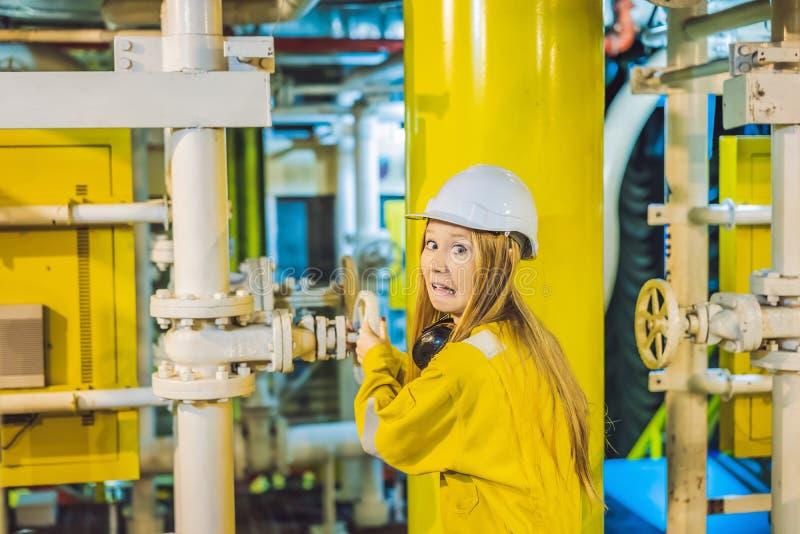 Jeune femme dans un uniforme jaune, les verres et le casque de travail dans le milieu industriel, la plateforme p?troli?re ou l'u photo stock