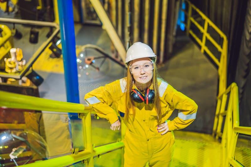 Jeune femme dans un uniforme jaune, les verres et le casque de travail dans le milieu industriel, la plateforme p?troli?re ou l'u photos stock