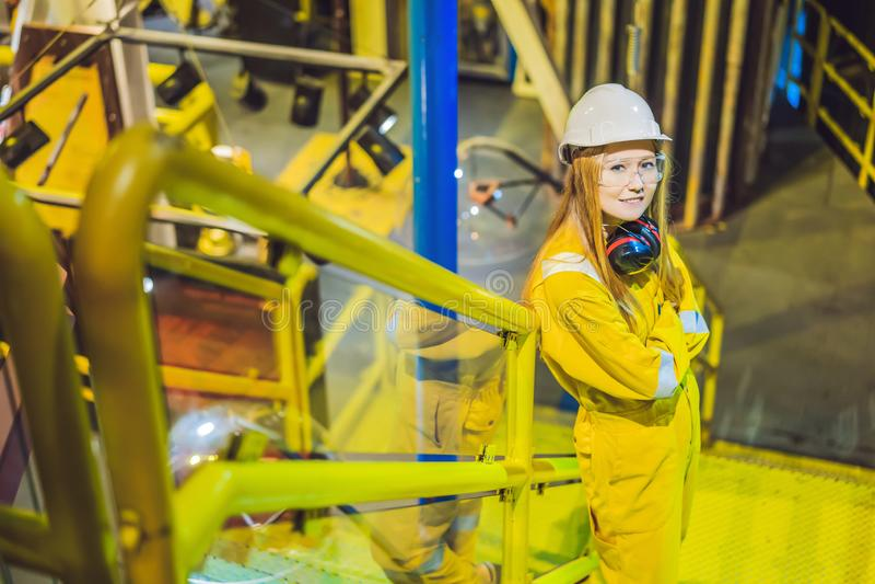 Jeune femme dans un uniforme jaune, les verres et le casque de travail dans le milieu industriel, la plateforme p?troli?re ou l'u photos libres de droits