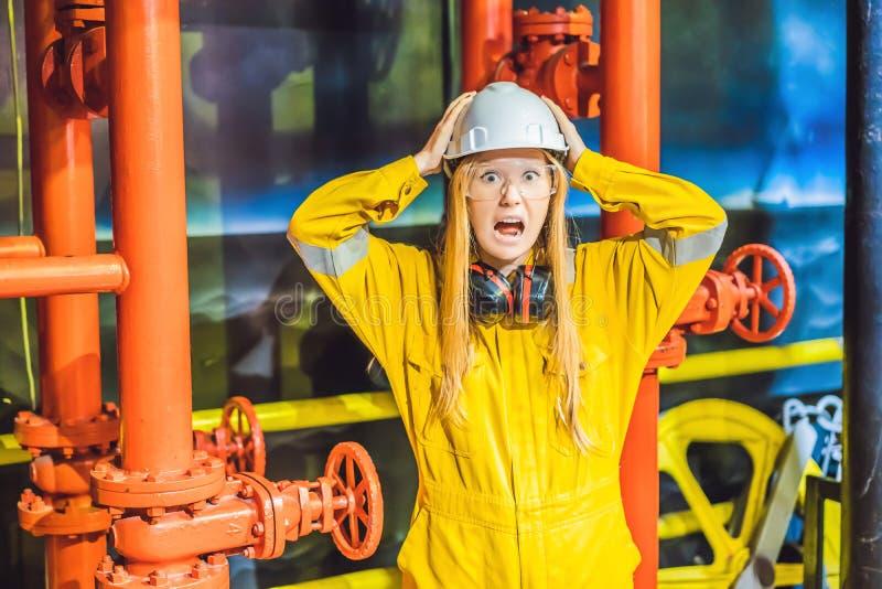 Jeune femme dans un uniforme jaune, les verres et le casque de travail dans le milieu industriel, la plateforme p?troli?re ou l'u image stock
