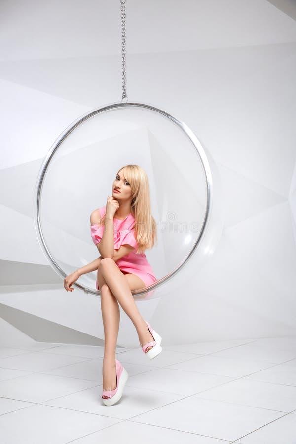 Jeune femme dans une chaise sur un fond blanc geometry Blonde dans une robe rose dans une chaise ronde en plastique photos stock
