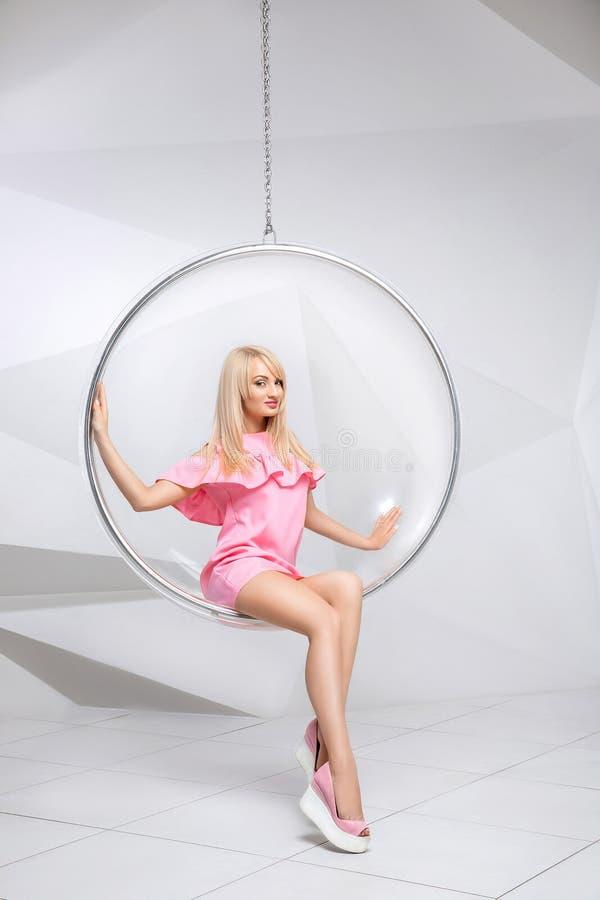 Jeune femme dans une chaise sur un fond blanc geometry Blonde dans une robe rose dans une chaise ronde en plastique photo stock