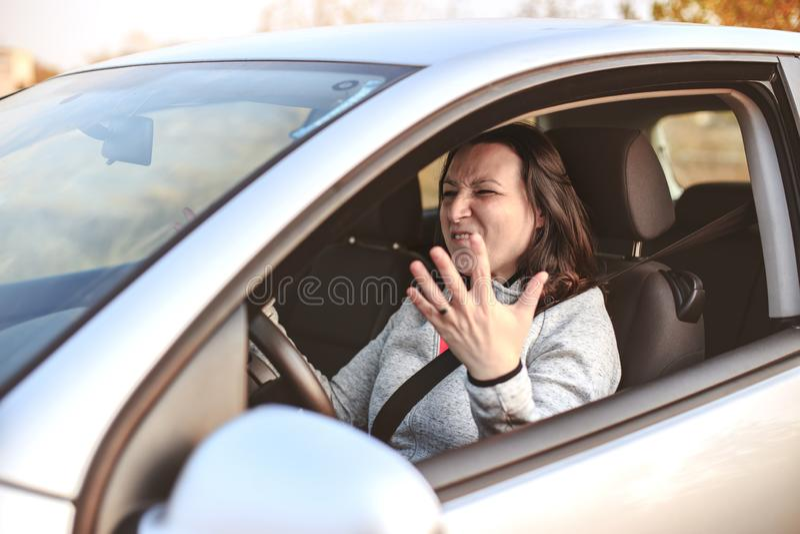 Jeune femme dans une crise nerveuse dans sa voiture images stock