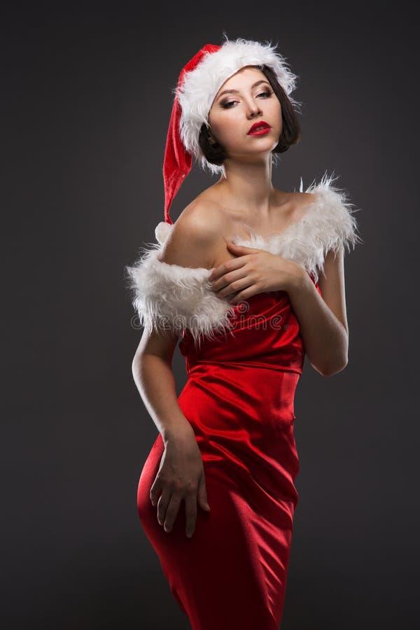 Jeune femme dans une jupe et un chapeau rouges du père noël sur un backgr léger images stock