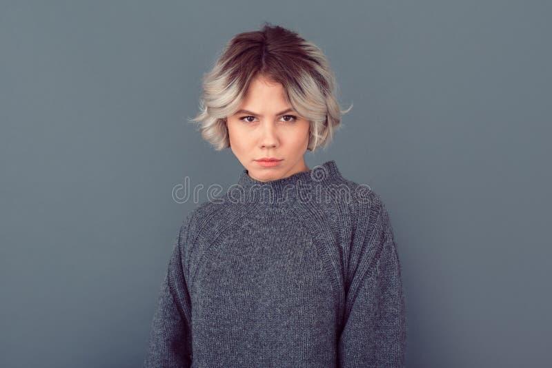 Jeune femme dans une photo grise de studio de chandail sur le fond gris prudent photo stock