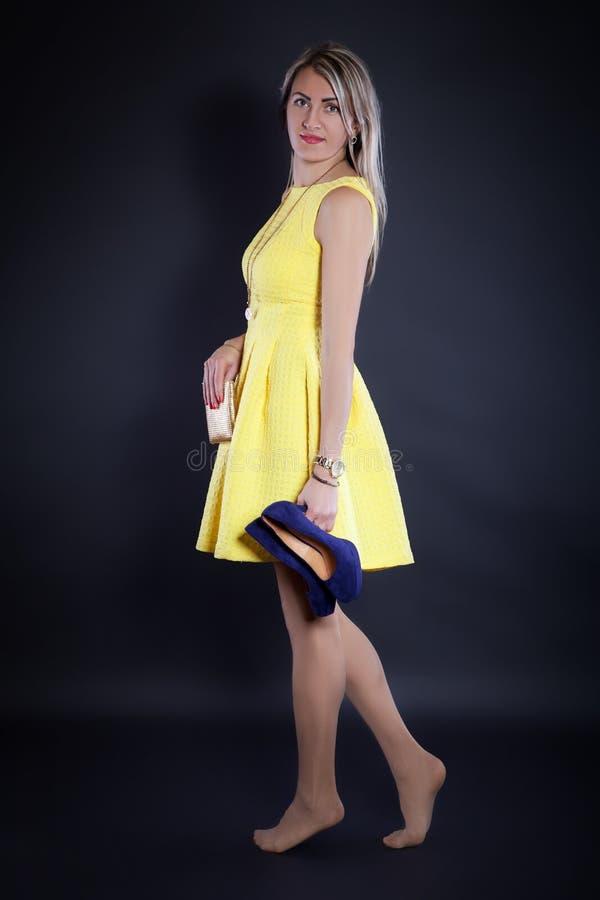 Jeune femme dans une robe jaune image stock
