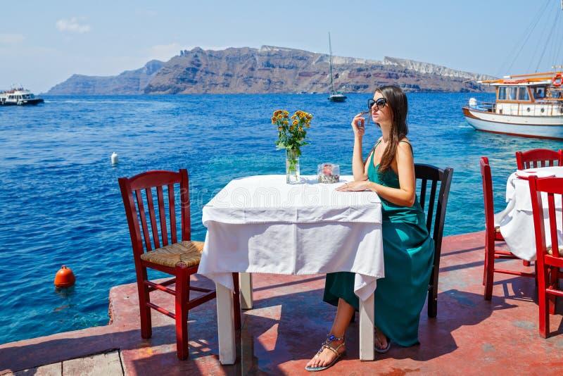 Jeune femme dans une robe se reposant à une table photos stock