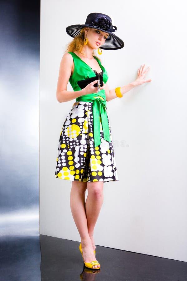 Jeune femme dans une robe verte et un chapeau noir photo libre de droits