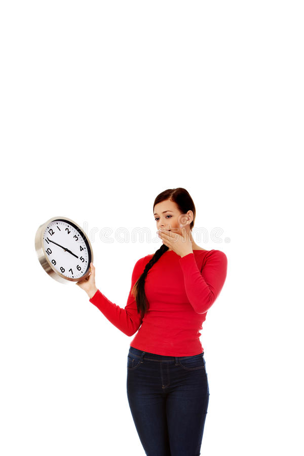 Jeune femme de baîllement tenant une horloge photos stock