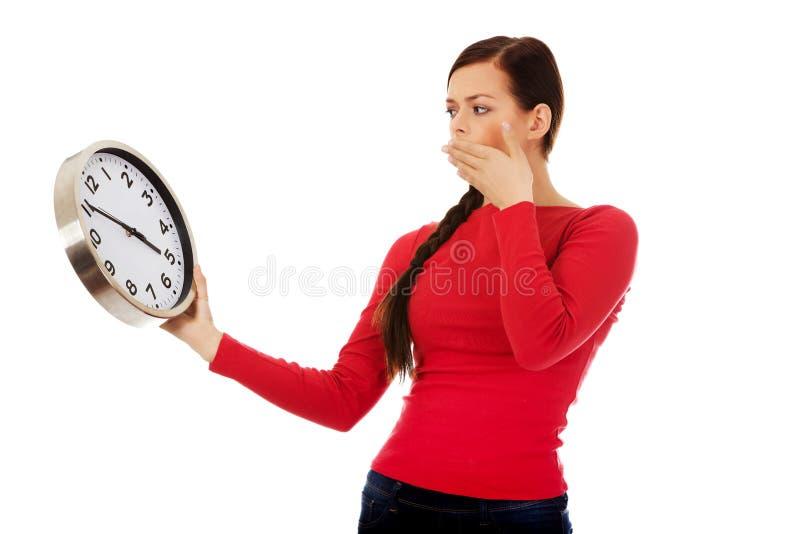 Jeune femme de baîllement tenant une horloge photo stock