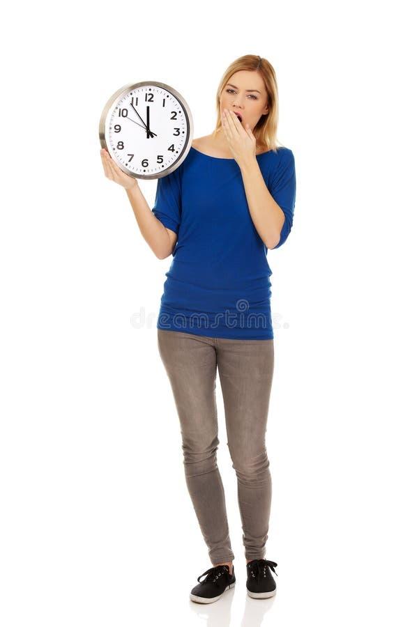 Jeune femme de baîllement tenant une horloge photos libres de droits