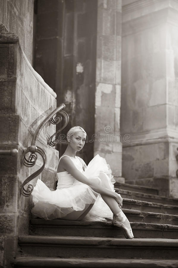 Jeune femme de ballerine posant sur des escaliers photo stock