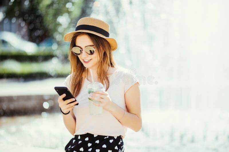 Jeune femme de beauté avec chating de téléphone ou ressac en macédoine de fruits de mojito de boissons d'Internet contre la fonta photo stock