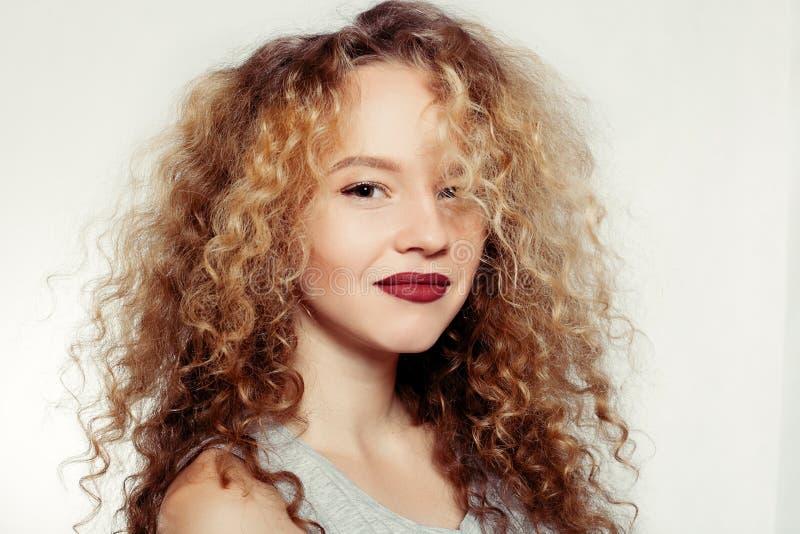 Jeune femme de beauté avec de grands et longs cheveux bouclés photographie stock libre de droits