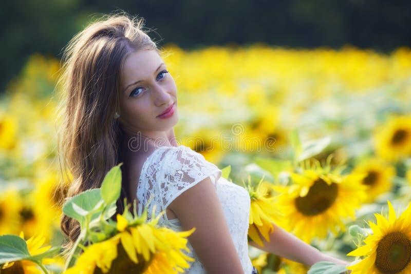 Jeune femme de beauté dans le domaine de tournesol photos stock