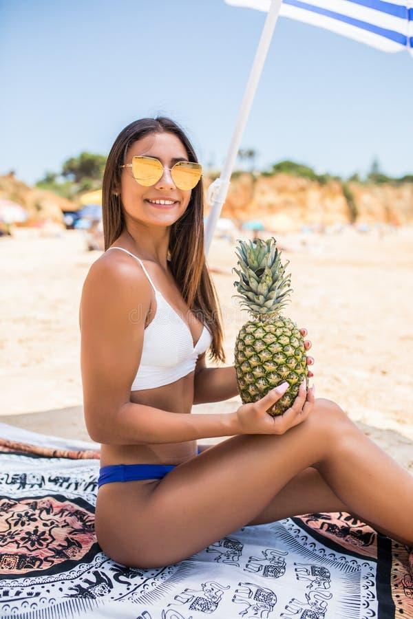 Jeune femme de beauté dans le maillot de bain d'ananas et le chapeau du soleil à la plage Vocation d'été image libre de droits