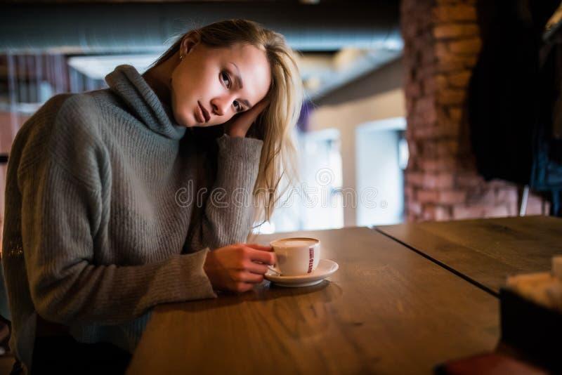 Jeune femme de beauté dans un café potable de café photo stock