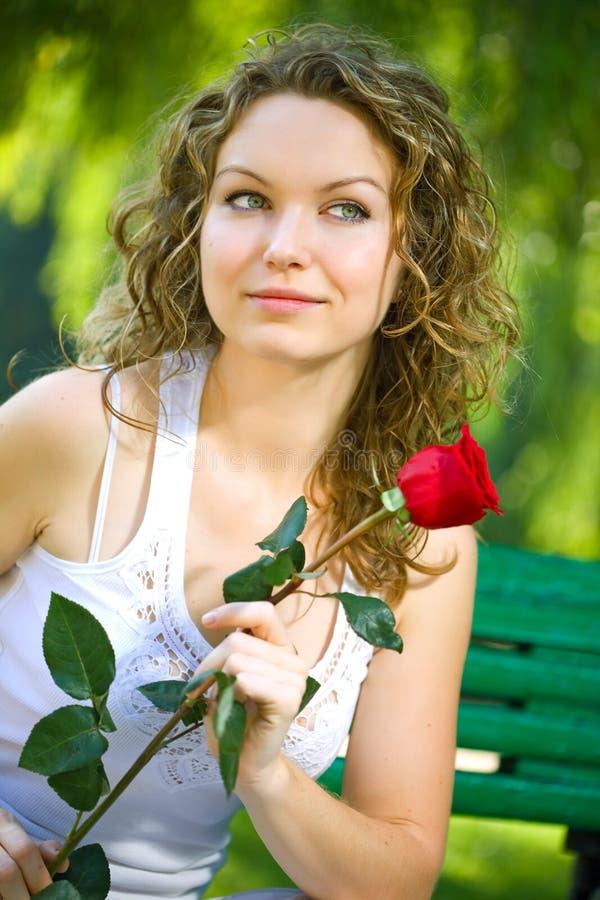 Jeune femme de beauté en stationnement avec la fleur image stock