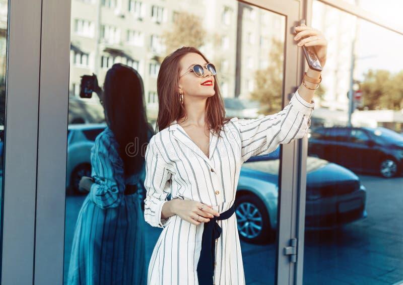Jeune femme de beauté faire le selfie pour le smartphone d'individu, port extérieur images stock