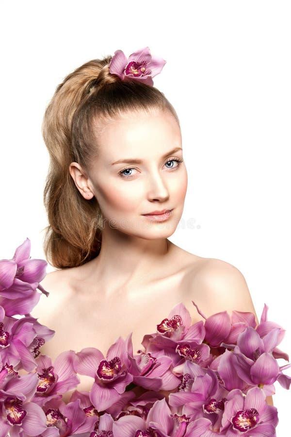 Jeune femme de beauté, longs cheveux bouclés de luxe avec la fleur d'orchidée coupe Peau saine fraîche de belles filles, maquilla photographie stock libre de droits