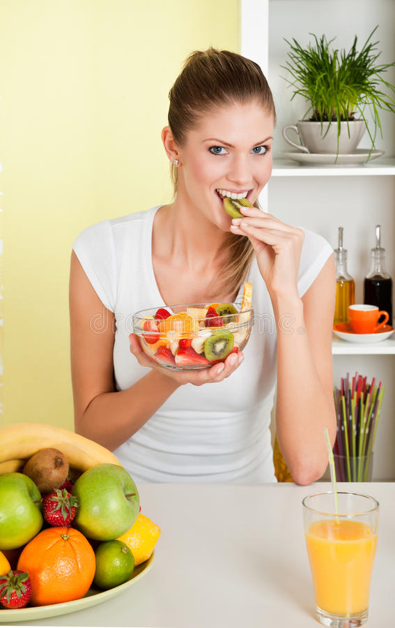 Jeune femme de beauté mangeant de la salade de fruits photo stock