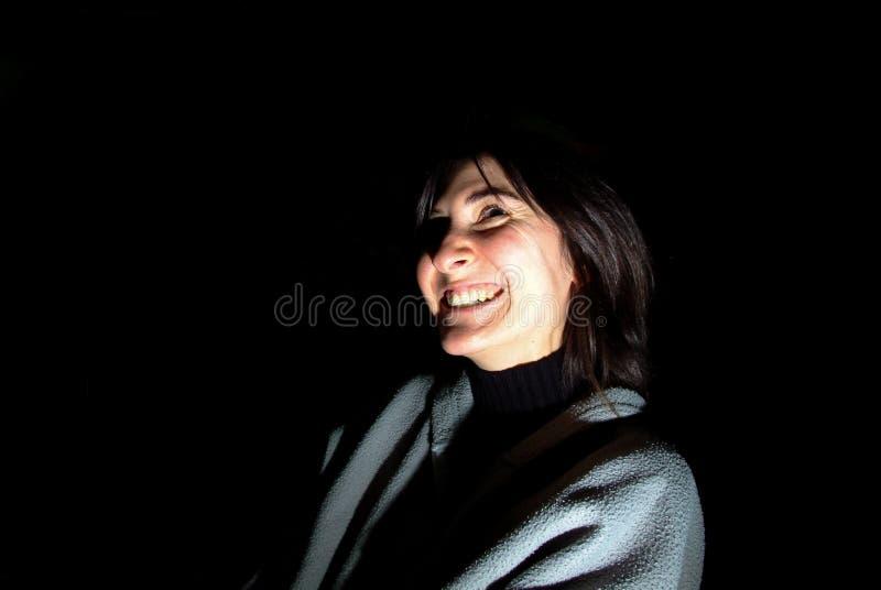 Jeune femme de brune avec le vêtement occasionnel souriant au-dessus du dos de noir photo libre de droits