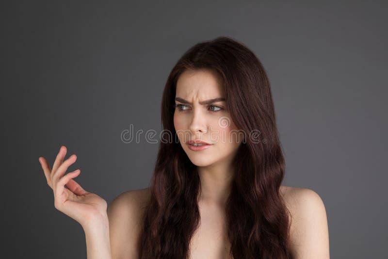 Jeune femme de brune avec les épaules nues souriant d'un air affecté de l'incrédulité fronçant les sourcils tout en se dirigeant  images libres de droits