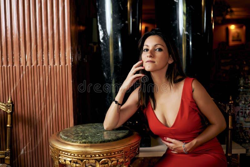 Jeune femme de brune avec une robe rouge dans le salon photographie stock libre de droits