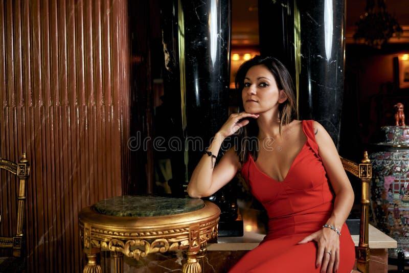 Jeune femme de brune avec une robe rouge dans le salon image stock