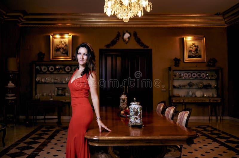 Jeune femme de brune avec une robe rouge dans le salon photo stock