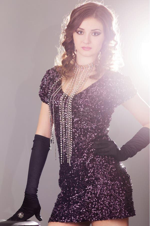 Jeune femme de brune dans la robe brillante noire image stock