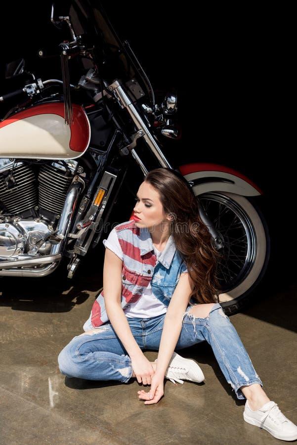 Jeune femme de brune dans le gilet de denim se reposant près de la moto et regardant loin images stock