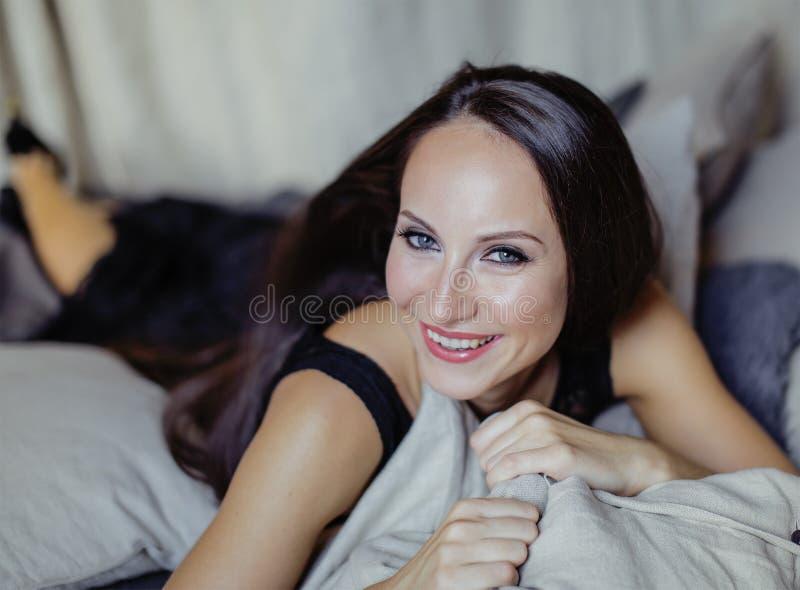 Jeune femme de brune de beauté dans l'intérieur à la maison de luxe, élégant gris de chambre à coucher féerique images libres de droits