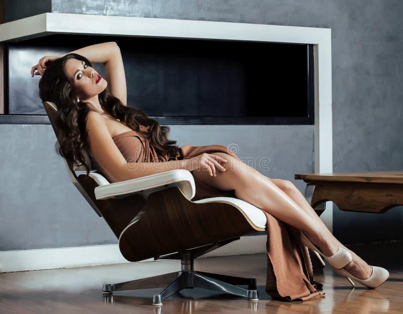 Jeune femme de brune de beauté s'asseyant près de la cheminée photos stock