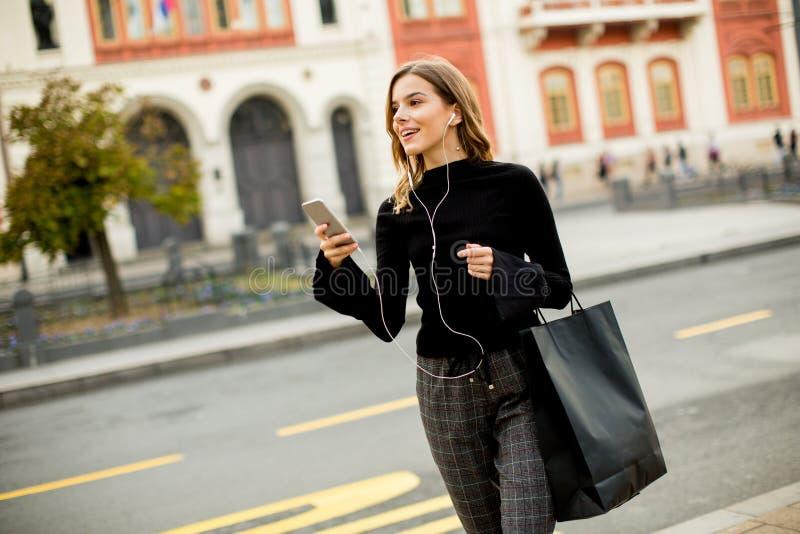 Jeune femme de brune employant le mobile tout en se tenant sur la rue et photo stock