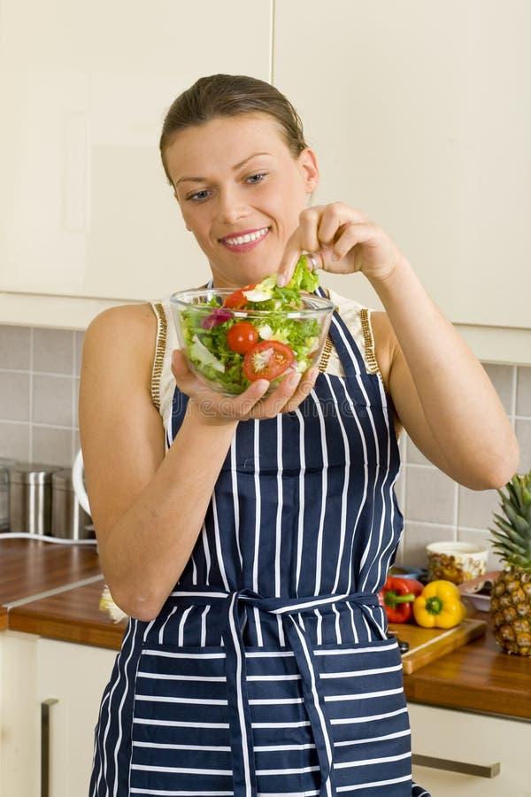 Jeune femme de brune mangeant d'une salade images libres de droits