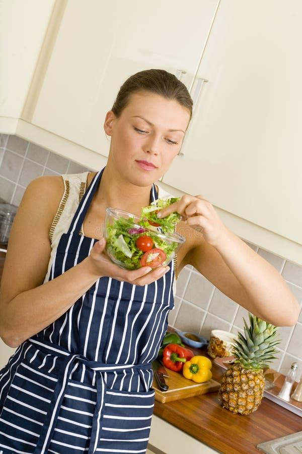 Jeune femme de brune mangeant d'une salade photo stock