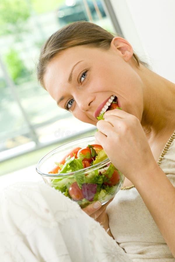 Jeune femme de brune mangeant d'une salade photos stock